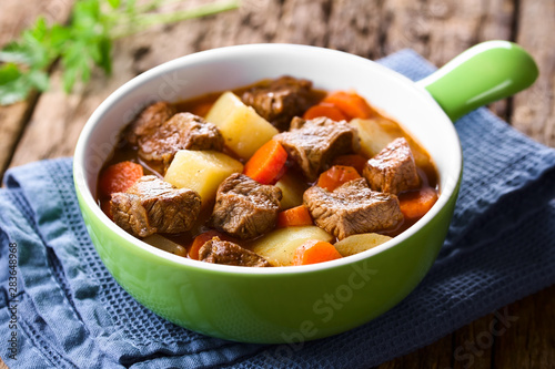Foto Fresh homemade beef stew with carrot and potatoes served in green bowl (Selectiv