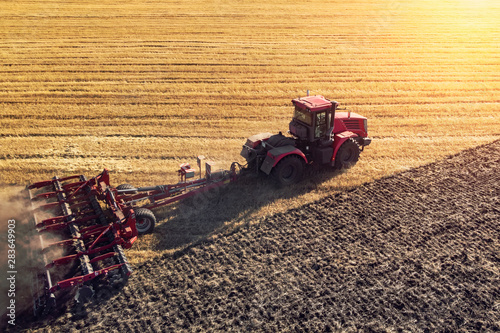 Agriculture machine harvesting crop in fields. Tractor pulls a mechanism for haymaking. Harvesting in autumn in the morning at dawn. agribusiness in the Altai region Russia.