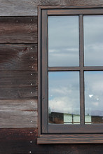 Large Window On A Wooden Building Reflecting The Sky On A Cloudy Overcast Day