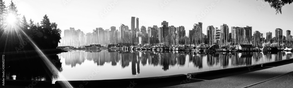 Black and white panoramic view of Vancouver skyline at sunrise as seen from Stanley Park, British Columbia, Canada.