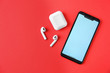 Leinwanddruck Bild - Wireless earphones, mobile phone and charging case on red background, flat lay. Space for text