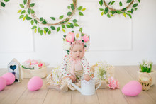 Cute Little Girl In A Dress With A Flower Print And A Hat With Flowers In The Easter Decorations In The Studio. Little Girl With Easter Eggs And Flowers In A Spring Studio