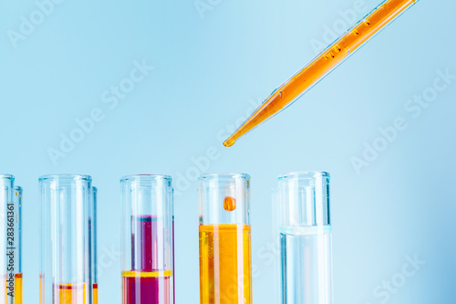 Photo  Laboratory test tubes with red and yellow liquids on light blue background