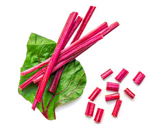 Creative Layout Made Of Fresh Rhubarb Or Rheum With Stalks, Leaves  And Pieces  Vegetable Isolated On White Background. Top View. Flat Lay.