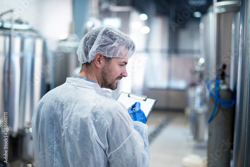 Fotomural  Technologist controlling production in factory.