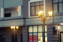Beautiful Classic Metal Street Lamp In Evening Against Modern Building In Evening. Warm Light Iron Retro Lantern At City Street At Twilight Time