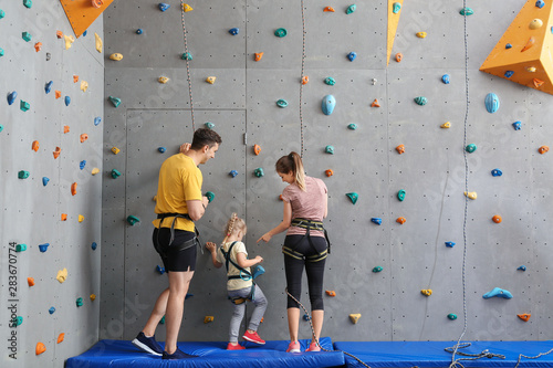 Photo Little girl with parents in climbing gym