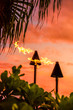 canvas print picture Hawaii luau party Maui fire tiki torches with flames burning against sunset sky clouds at night. Hawaiian culture travel background.