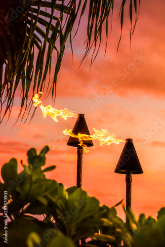 mata magnetyczna Hawaii luau party Maui fire tiki torches with flames burning against sunset sky clouds at night. Hawaiian culture travel background.