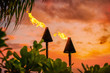 Leinwanddruck Bild - Hawaii luau party Maui fire tiki torches with open flames burning at sunset sky clouds at night. Hawaiian cultural travel vacation background.