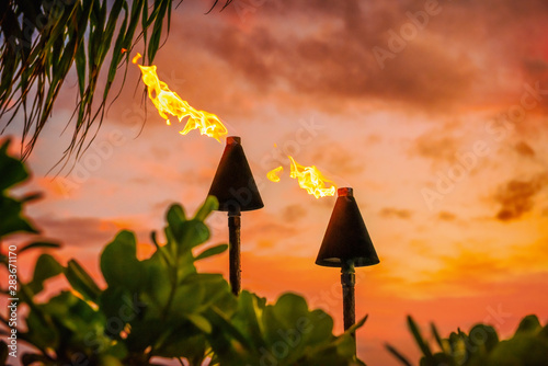 mata magnetyczna Hawaii luau party Maui fire tiki torches with open flames burning at sunset sky clouds at night. Hawaiian cultural travel vacation background.