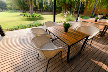 Wooden Chair With Table And Green Flora On Patio