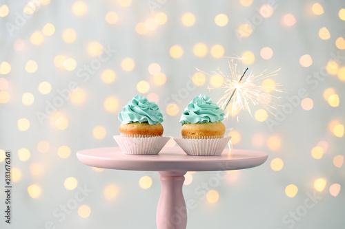 Tasty Birthday cupcakes on stand against defocused lights