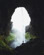 Wasserfall in einer Höhle in Island mit kleiner Person im Sommer