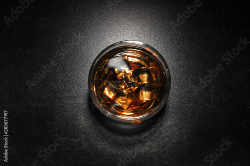 Poster de jardin Bar Glass of cold whiskey with ice on dark table