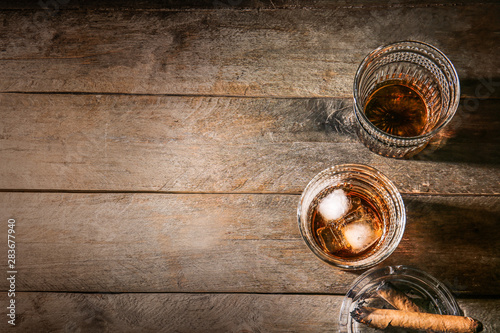 Foto auf Leinwand Alkohol Glasses of cold whiskey with cigars on wooden table