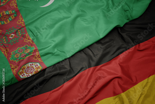 Photo waving colorful flag of germany and national flag of turkmenistan