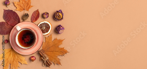 Staande foto Thee Autumn Flat lay composition. Cup of tea, autumn dry bright leaves, roses flowers, orange circle, cones, decorative pomegranate, cinnamon sticks on brown beige background top view. Autumn, fall concept