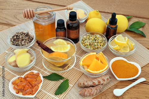 Alternative medicine for cold and flu remedy with hot drink, herbs and spices, lemon and orange fruit, aromatherapy oils, honey, lemon and orange fruit and vitamin tablets on bamboo Wallpaper Mural