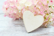 White Heart And Flowers Hydrangea Lying On Wood