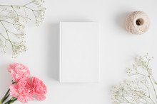 Top View Of A Book Mockup With A Bouquet Of Pink Carnations, Workspace Accessories And A Gypsophila  On A White Table.