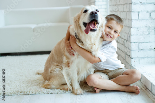 A child with a dog. Beautiful boy at home with a dog.  - 283716901