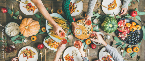 Obraz Vegan, vegetarian Thanksgiving, Friendsgiving holiday celebration. Flat-lay of friends clinking glasses at Thanksgiving Day table with pumpkin pie, vegetables, fruit, wine, top view, wide composition - fototapety do salonu