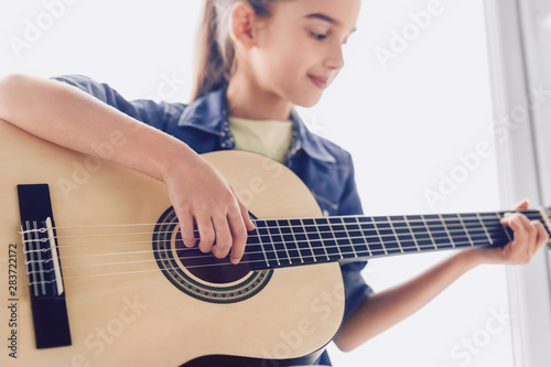 Obraz Girl learning to play guitar - fototapety do salonu