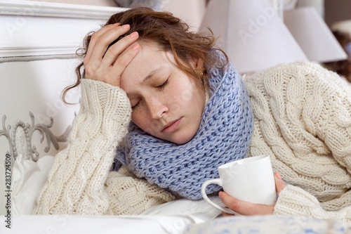 Fotografia  Sad alone young woman in white sweater and blue scarf feeling headache, cold sick and resting home in bed