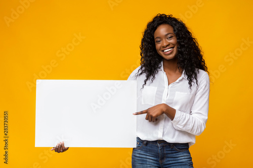 Fotografía  Afro girl is holding yellow advertising board