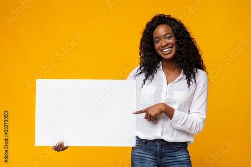 Fényképezés  Afro girl is holding yellow advertising board