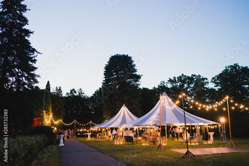 Obraz Coziness and style. Modern event design. Lounge zone and wedding reception decorations outdoors in the evening. - fototapety do salonu