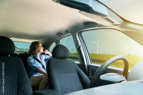 Woman passenger sitting in the backseat and looking out the window when her self-driving car rides on the highway.