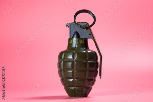 Green metal hand Grenade with round pin over When I pull out it will blow Bomb On a pink background - 283734339