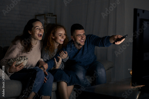 Fotografía Excited friends watching TV and switching channels
