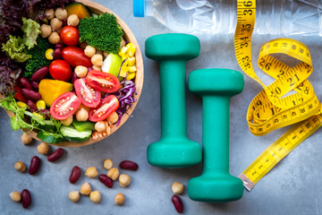Fresh vegetable salad and healthy food for sport equipment for women diet slimming with measure tap for weight loss on wood background. Healthy Sport Concept.