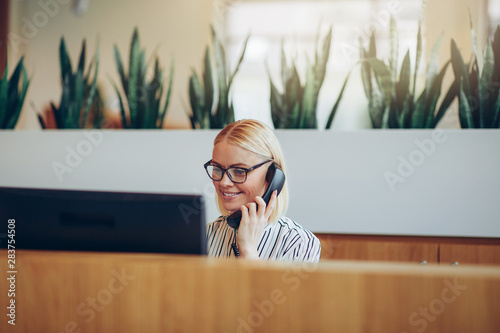 Smiling businesswoman talking on the telephone at a reception de Fototapeta
