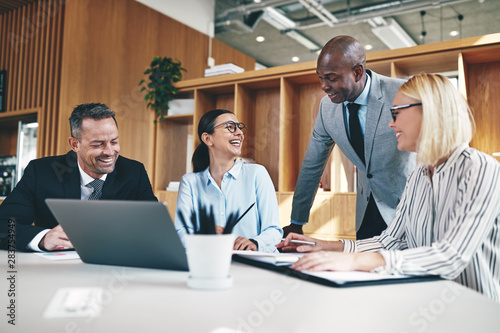 Group of diverse businesspeople laughing together during an offi Wallpaper Mural