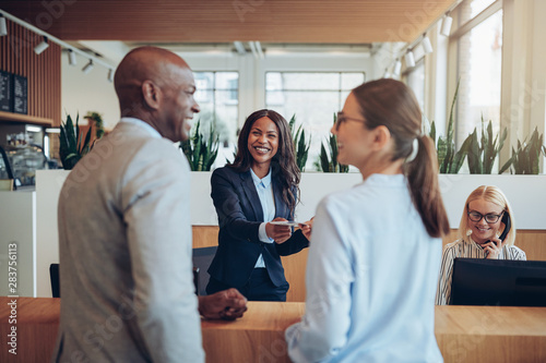 Photo Smiling concierge helping two guests check in to a hotel