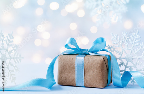 Fotografía  Beautiful Christmas composition with gift or present box and decorative snowflakes against holiday lights background