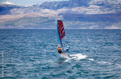 Young windsurfer in the waves in the sea