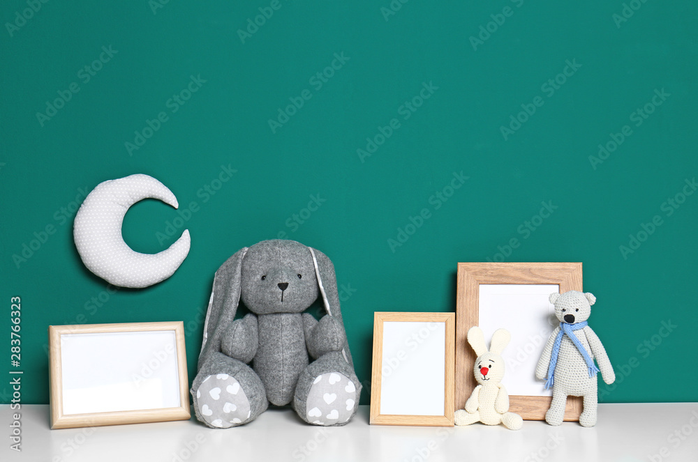 Fototapety, obrazy: Soft toys and photo frames on table against green background, space for text. Child room interior