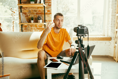 Fotografia, Obraz  Young caucasian male blogger with professional camera recording video review of gadgets at home