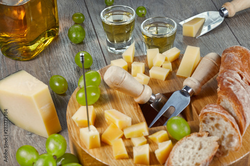 Fotografie, Obraz Grappa in small glasses with cheese, bread and grapes