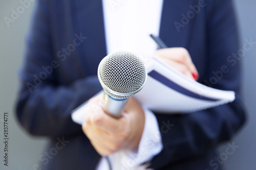 Spoed Foto op Canvas Londen Female journalist at news conference or media event, writing notes, holding microphone