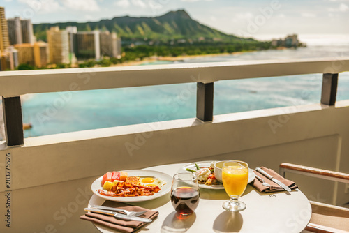 Hotel room breakfast on balcony view of Waikiki beach, Honolulu, Hawaii. Vacation travel morning food American breakfast in luxury resort outside.