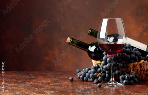 Juicy blue grapes and bottles of red wine on a brown background. Billede på lærred