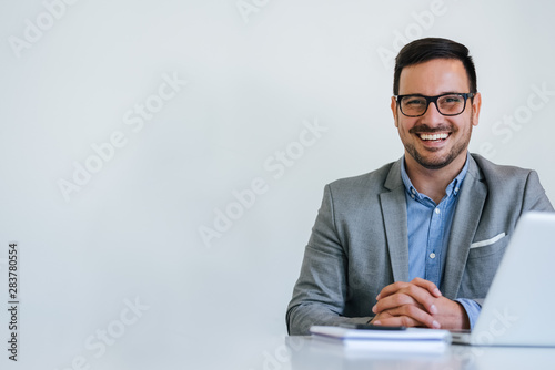 Fotomural Portrait of young smiling cheerful businessman in office looking at camera copy