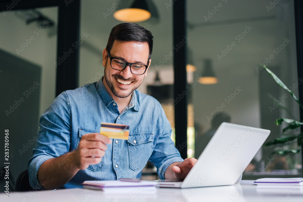 Fototapeta Happy cheerful smiling young adult man doing online shopping or e-shopping satisfied entrepreneur making online payment paying for service or goods self employed freelancer collecting fee