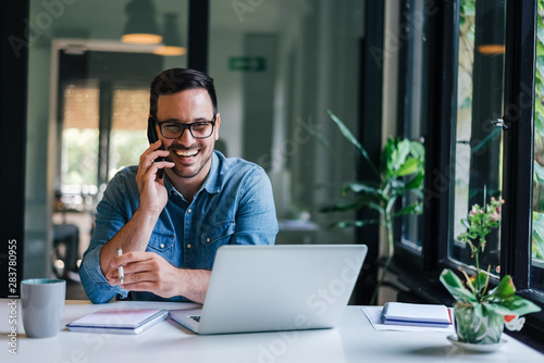Portrait of young smiling cheerful entrepreneur in casual office making phone call while working with laptop